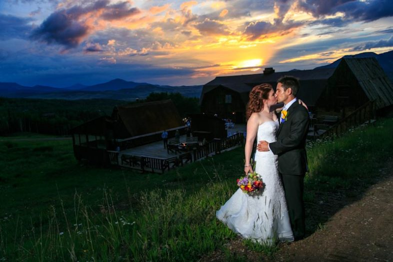 Bride and groom posing for an intimate portrait at sunset with Gorrono and the Wilson Range in the background
