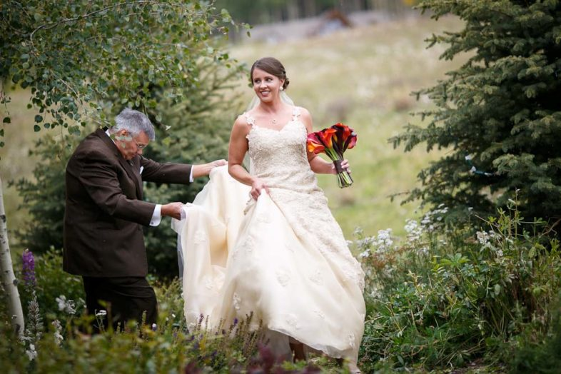 The bride's father carrying her train