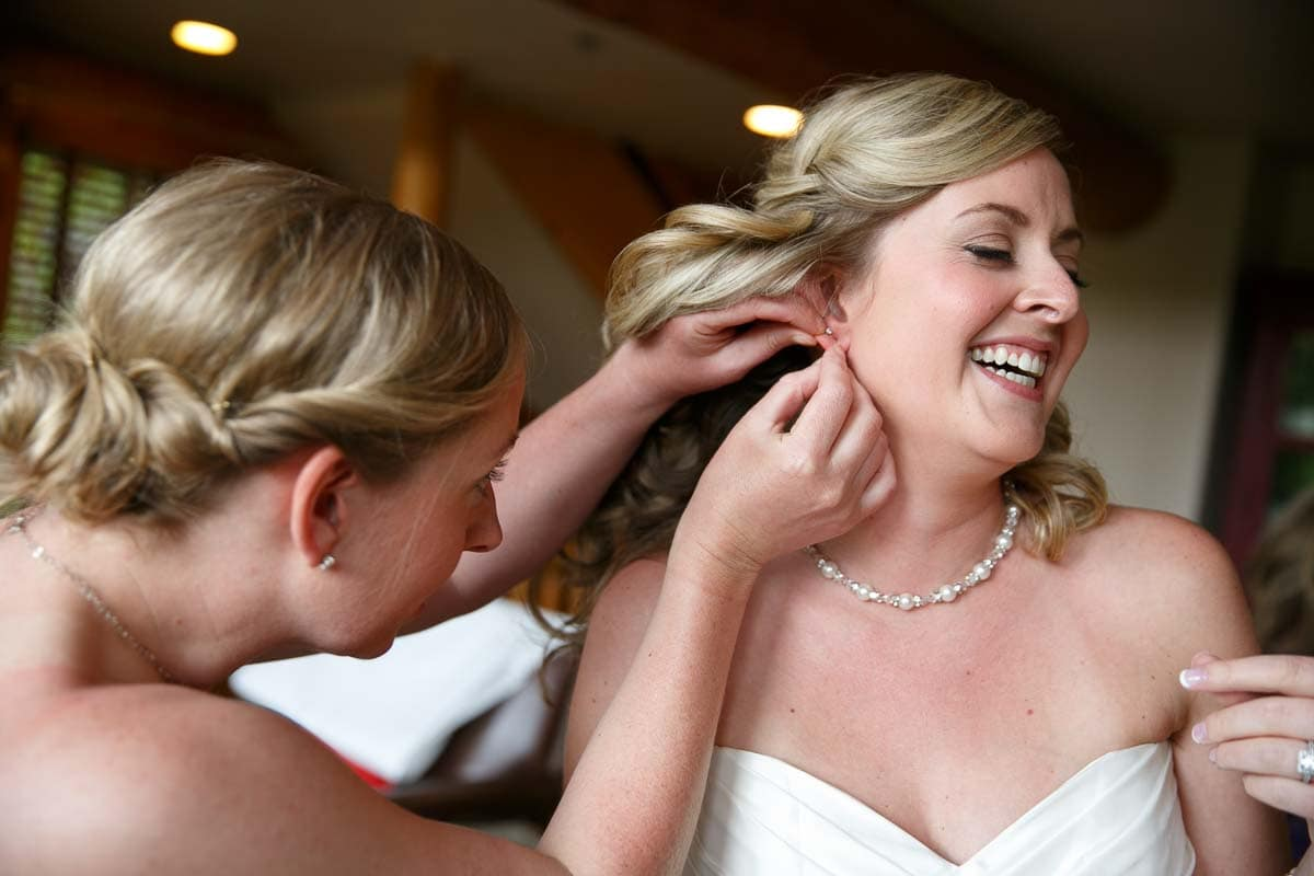Bridesmaid helping the bride with her earrings
